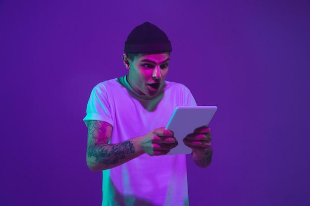 Il ritratto dell'uomo caucasico isolato sul fondo dello studio di pendenza alla luce al neon