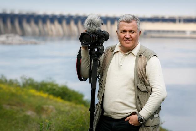 Il ritratto dell'uomo con la fotocamera e il treppiede