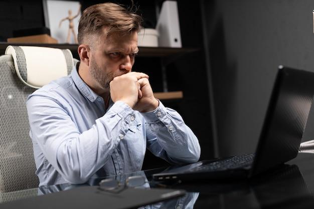 Il ritratto dell'uomo d'affari serio, osserva nel monitor del computer portatile