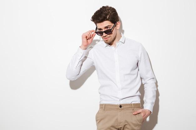 Il ritratto dell'uomo sessuale sessuale si è vestito in camicia che guarda a parte da sotto gli occhiali da sole, sopra spazio bianco con ombra