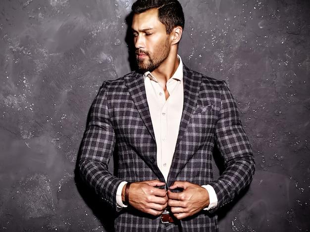 Il ritratto dell'uomo sexy di modello maschio di modo bello sexy si è vestito in vestito elegante che posa vicino alla parete grigia