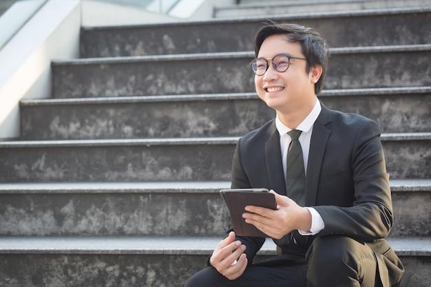 Il ritratto dell'uomo sorridente di affari sembra sicuro facendo uso della compressa del computer