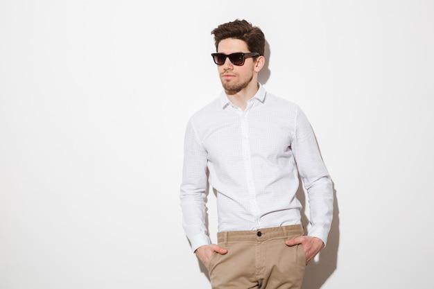 Il ritratto dell'uomo unshaved alla moda si è vestito in camicia ed occhiali da sole che posano sulla macchina fotografica con le mani in tasche, sopra spazio bianco con ombra