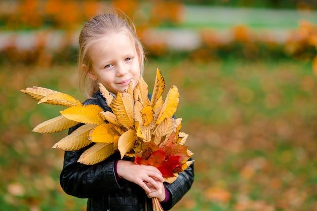 Il ritratto della bambina adorabile con giallo e l'arancio lascia il mazzo all'aperto al bello giorno di autunno