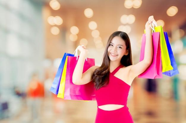 Il ritratto della donna asiatica porta il sacchetto della spesa rosso della tenuta del vestito con il sorriso e felice