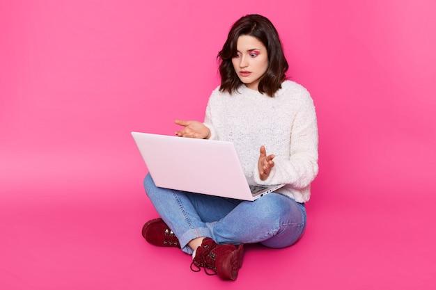 Il ritratto della donna casuale sorpresa si siede sul pavimento con il computer portatile