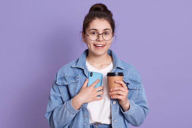Il ritratto della donna caucasica sorridente che sta contro la parete lilla con porta via il caffè