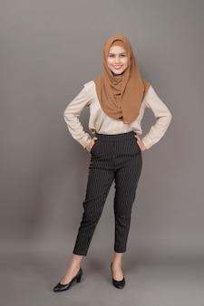 Il ritratto della donna con hijab sta sorridendo su gray