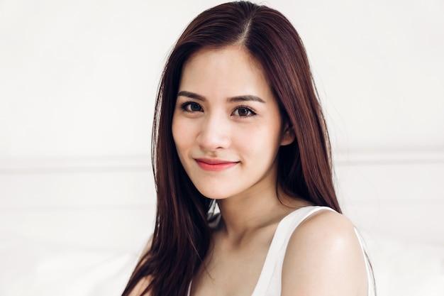 Il ritratto della donna dell'asia gode di e si rilassa sul letto in camera da letto a casa bellezza asiatica