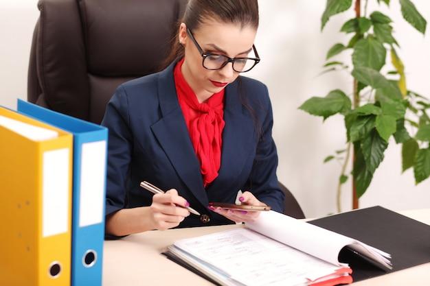Il ritratto della donna di affari con il computer portatile scrive su un documento nel suo ufficio