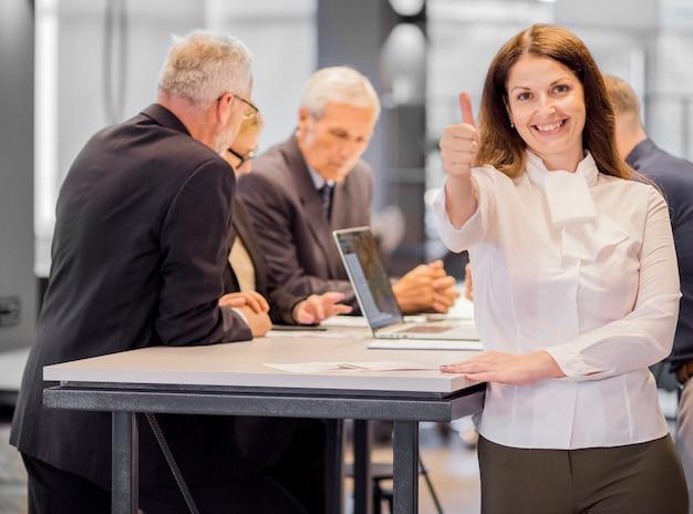 Il ritratto della donna di affari sorridente nel luogo di lavoro che mostra il pollice aumenta il segno