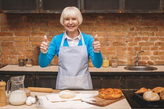Il ritratto della donna invecchiata senior attraente sta cucinando sulla cucina. nonna che produce una cottura saporita. pollice su.