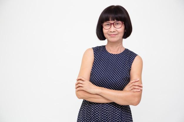 Il ritratto della donna senior asiatica con le armi ha attraversato isolato