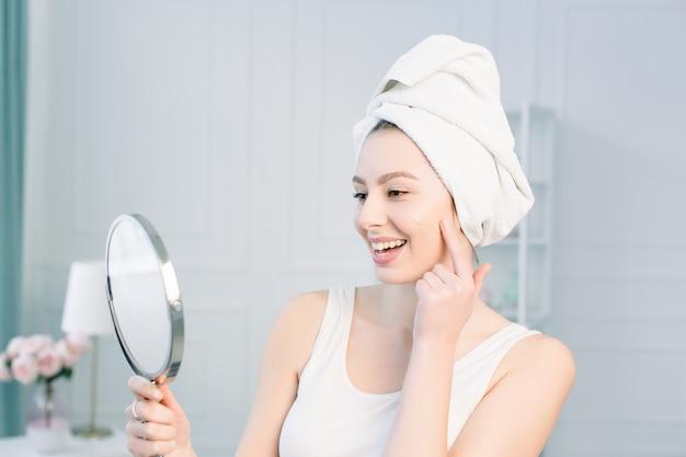 Il ritratto della donna sorridente caucasica attraente sullo studio bianco ha sparato pulendo il suo fronte che esamina lo specchio che applica il fondamento sulla pelle facciale