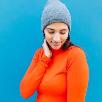 Il ritratto della donna timida che guarda giù l'uso tricotta il cappello contro fondo blu