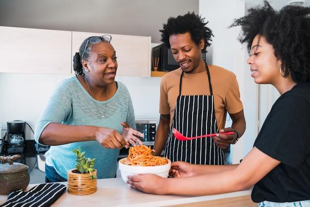 Il ritratto della famiglia cucina insieme a casa.