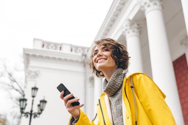 Il ritratto della femmina contenta 20s che tiene l'aggeggio moderno riceve il messaggio di testo sul suo smartphone mentre è all'aperto