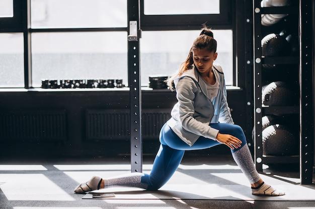 Il ritratto della giovane donna attraente che fa l'yoga o i pilates si esercita