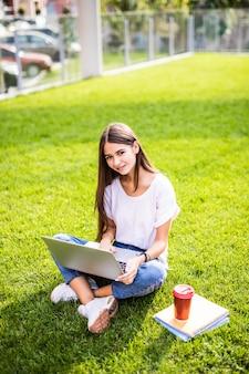 Il ritratto della giovane donna attraente che si siede sull'erba verde in parco con le gambe ha attraversato durante il giorno di estate mentre per mezzo del computer portatile