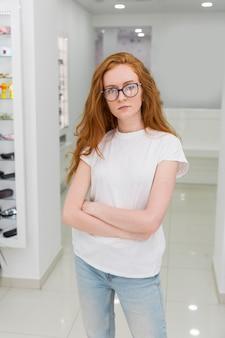 Il ritratto della giovane donna attraente con il braccio ha attraversato la condizione allo showroom di ottica