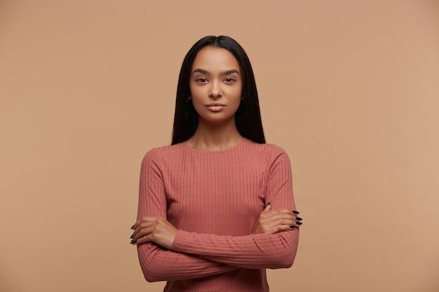 Il ritratto della giovane donna castana calma, sicura, attraente sta con le braccia attraversate