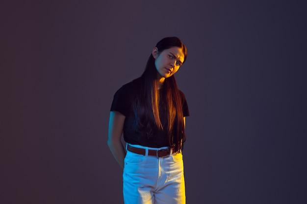 Il ritratto della giovane donna caucasica isolato sul fondo dello studio alla luce al neon.