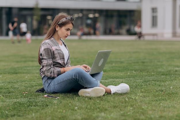 Il ritratto della giovane donna che si siede nel parco con le gambe ha attraversato durante il giorno di estate mentre per mezzo del computer portatile