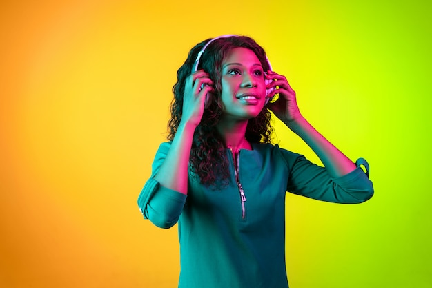 Il ritratto della giovane donna isolato sulla parete di pendenza alla luce al neon