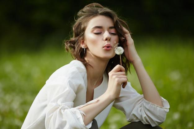 Il ritratto della primavera di una ragazza che si siede in un campo sull'erba fra il dente di leone fiorisce.
