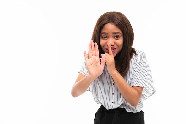 Il ritratto della ragazza africana che possing e gesticola le mani sopra