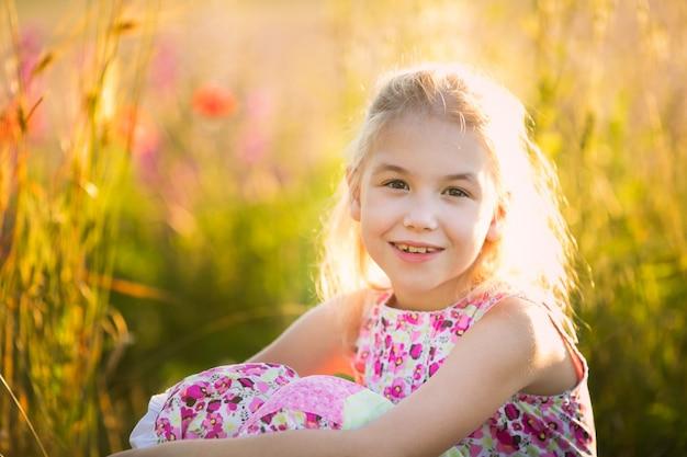 Il ritratto della ragazza bionda che fa sedere nel campo del fiore n il tramonto.