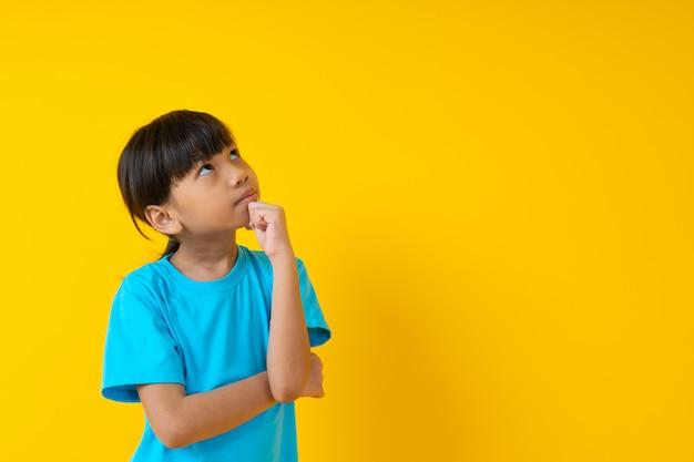 Il ritratto della ragazza che pensa e ottiene l'idea, il bambino tailandese dello studente nella condizione blu molle della camicia e indovina isolato
