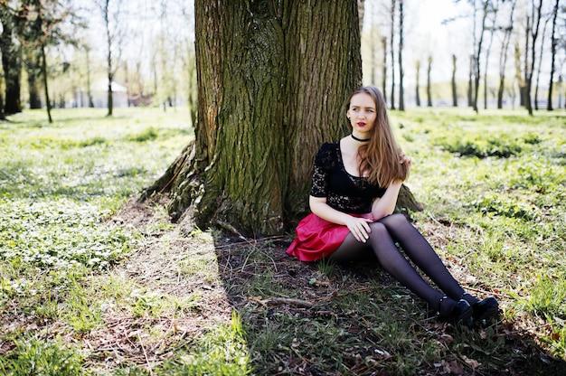 Il ritratto della ragazza con luminoso compone con le labbra rosse, la collana nera del choker sul suo collo e la gonna di cuoio rossa che si siedono vicino all'albero al parco.