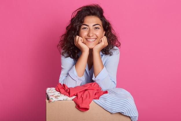 Il ritratto della ragazza mora attraente sveglia sta vicino alla scatola di cartone