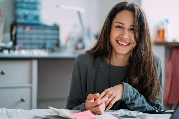 Il ritratto della ragazza sorridente sveglia dei pantaloni a vita bassa con gli esercizi dell'istituto universitario di scrittura in taccuino.