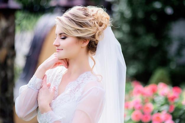 Il ritratto della sposa affascinante in abito di seta bianco sta nel giardino soleggiato
