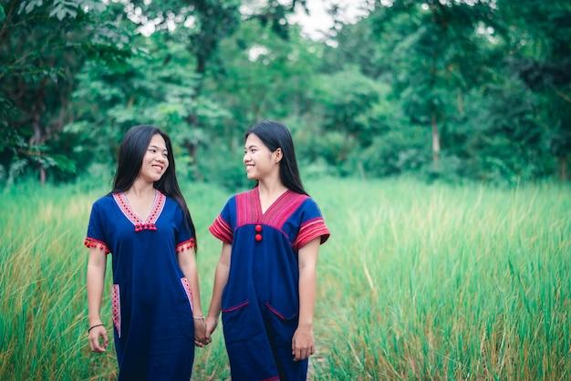 Il ritratto delle ragazze gode di di giocare nella foschia di foresst all'aperto alla campagna della tailandia