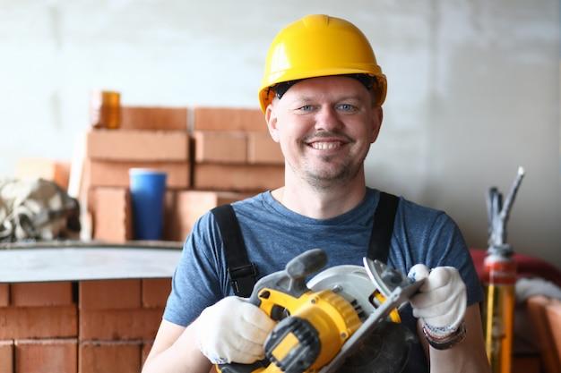 Il ritratto dello specialista esperto che tiene la sega elettrica con attenzione e con gioia. uomo felice con strumenti nuovi e moderni per facilitare il lavoro. concetto di costruzione
