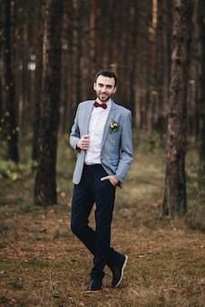 Il ritratto dello sposo attraente in giacca e cravatta con boutonniere o asola sulla giacca, è in piedi sullo sfondo della foresta in natura.