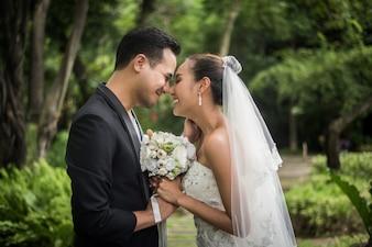 Il ritratto dello sposo di giorno delle nozze di amore dà il mazzo dei fiori alla sua sposa.