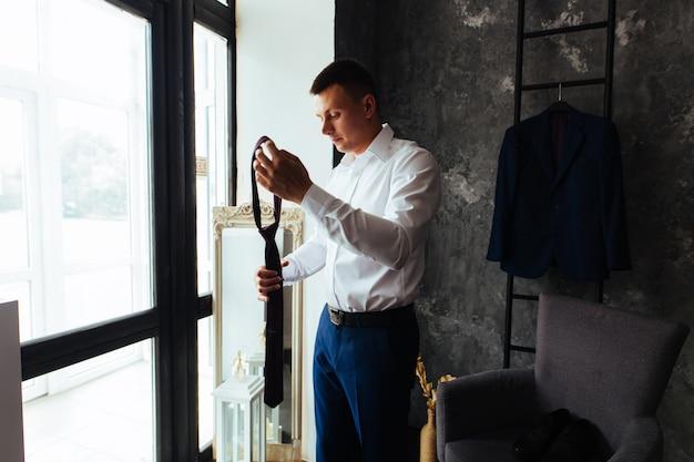 Il ritratto dello studio dello sposo in camicia bianca regola una cravatta rossa. mattina degli sposi. giovane uomo sorridente in camicia bianca e pantaloni neri regola la cravatta. ragazzo elegante indossa un tailleur in interni eleganti.