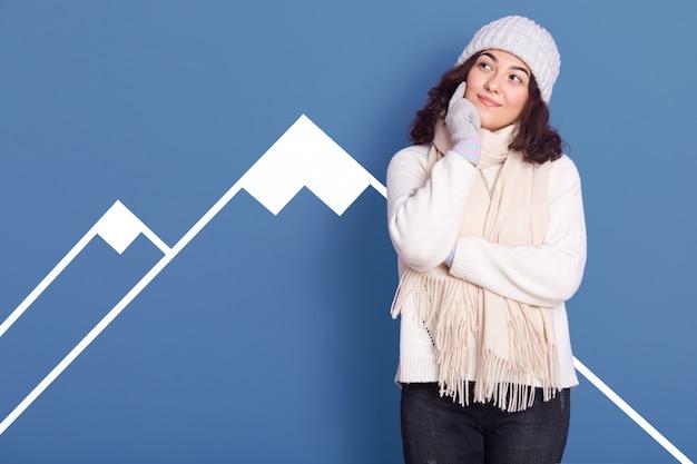 Il ritratto dello studio di giovane ragazza caucasica attraente veste i vestiti dell'inverno