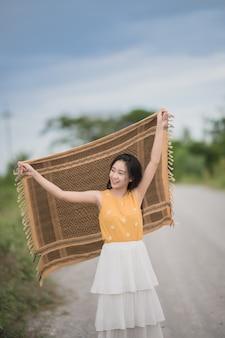 Il ritratto di bella donna asiatica felice tiene una sciarpa. femmina asiatica all'aperto.