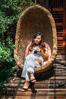 Il ritratto di bella donna asiatica si distende al caffè