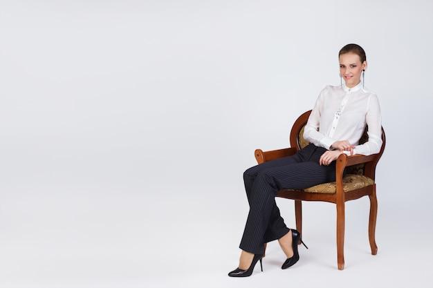 Il ritratto di bella giovane ragazza sorridente di affari in una blusa bianca, i pantaloni neri e le scarpe nere siede una poltrona isolata