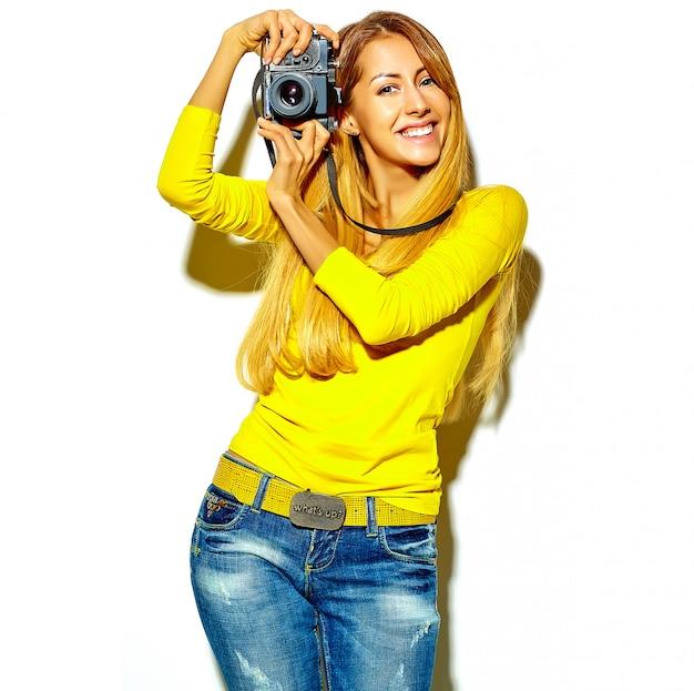 Il ritratto di bella ragazza bionda sorridente felice sveglia della donna in vestiti casuali dell'estate prende le foto che tengono la retro macchina fotografica, isolata su un bianco