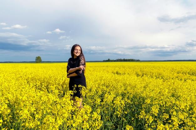 Il ritratto di bella ragazza con capelli lunghi in vestito nero sta stando nel campo giallo.