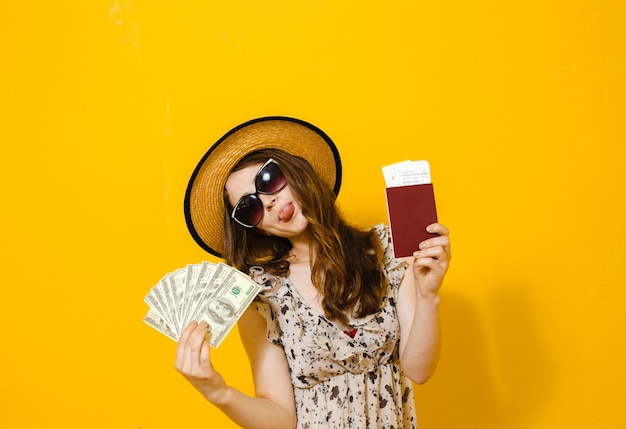 Il ritratto di bella ragazza felice del brunette che tiene i biglietti e il passaporto di viaggio delle banconote dei soldi