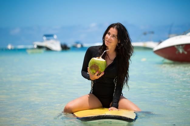 Il ritratto di bella ragazza praticante il surfing con la noce di cocco verde dalla palma si siede sul bordo giallo del surf del longboard della spuma