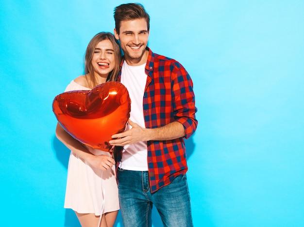 Il ritratto di bella ragazza sorridente e del suo ragazzo bello che tengono il cuore hanno modellato i palloni e la risata. coppia felice in amore. buon san valentino. posing